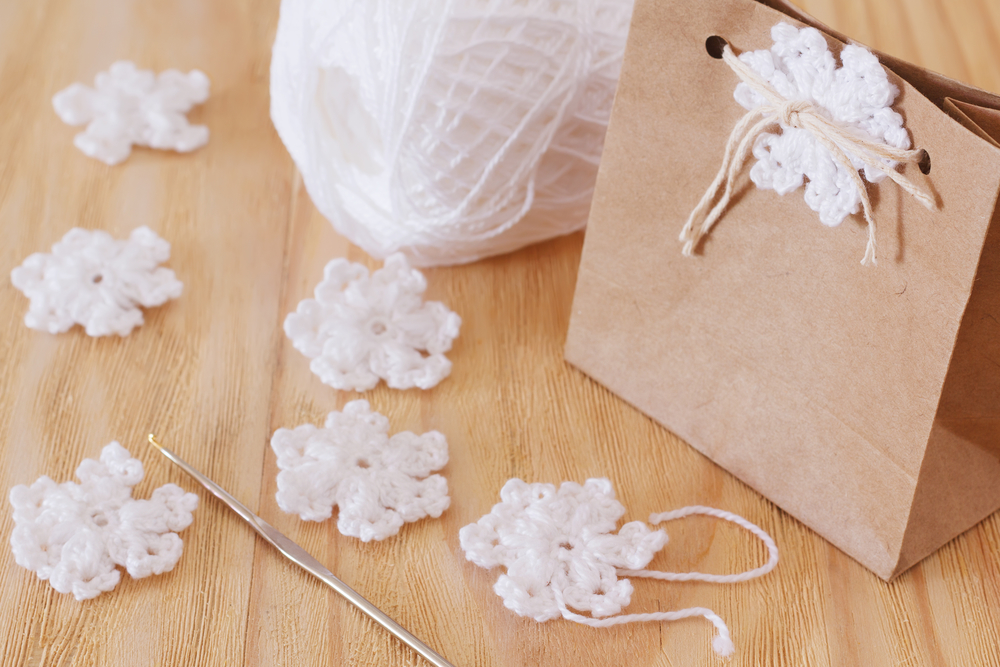 White crochet snowflakes for Christmas decoration of package gift. Selective focus